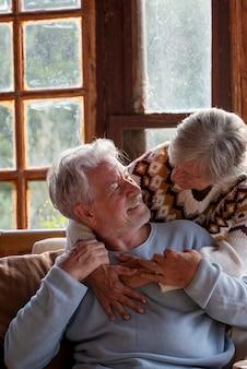 家でお互いを見て恋をしている幸せな高齢者のライフスタイルの高齢者。女性は抱擁し、老人が笑っているのを見てください。引退したカップルのための冬の季節と屋内での余暇活動