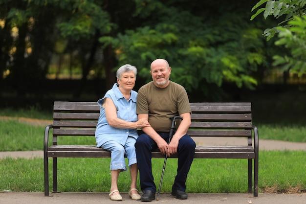 Счастливый пожилой мужчина и женщина-инвалид сидят на скамейке на открытом воздухе в летнем парке