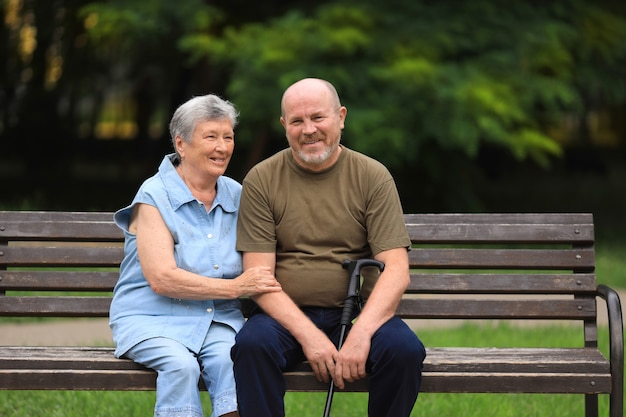 Happy elderly man and disabled woman sitting on bench outdoors