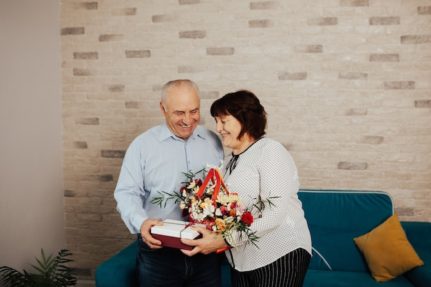 The happy elderly man giving flowers and a gift to a his wife.