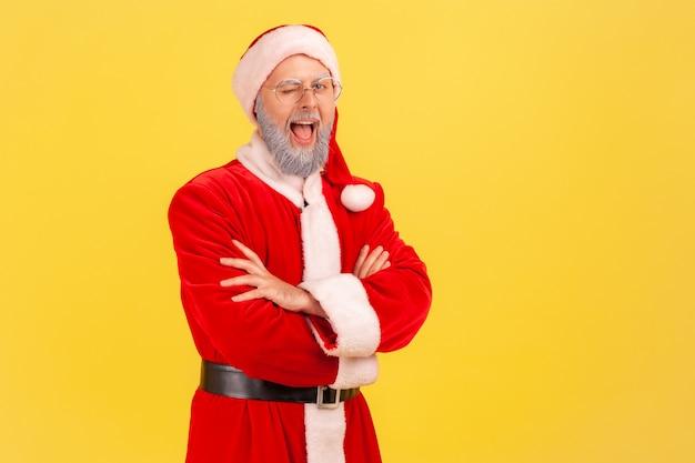サンタクロースの衣装を着た幸せな老人は、腕を組んで立って、カメラを見て、まばたきをして、口を開けたままです。黄色の背景に分離された屋内スタジオショット。