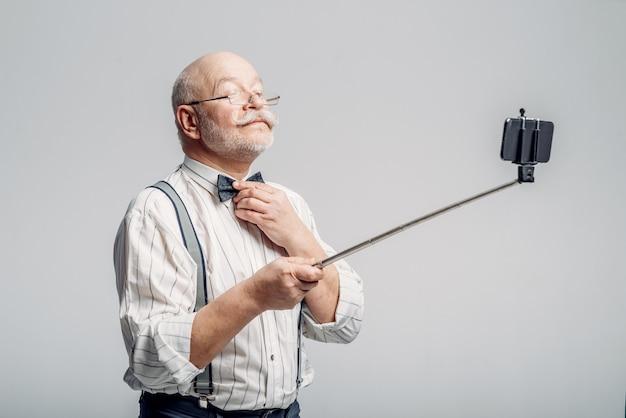 Happy elderly man makes selfie on phone.
