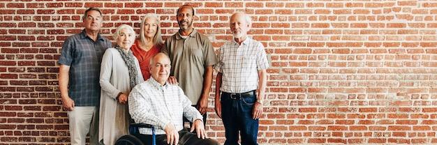 Счастливый пожилой мужчина на инвалидной коляске с друзьями