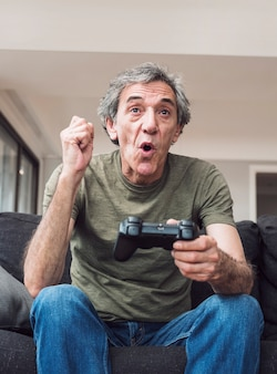 Happy elderly man playing video game