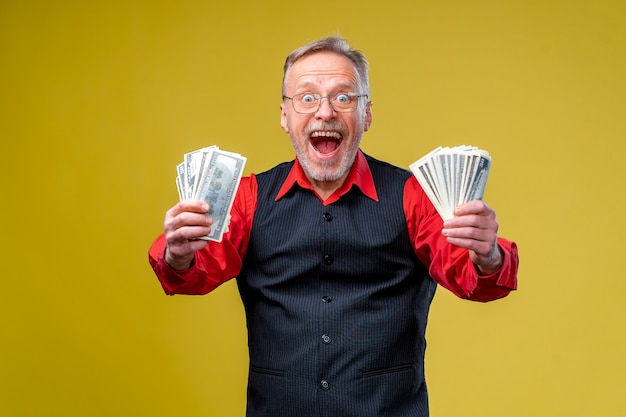 Happy elderly man showing two bunches of money.