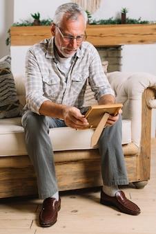 Felice uomo anziano seduto sul divano guardando la cornice della foto
