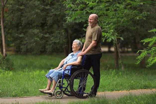 車椅子を屋外に座っている無効になっている高齢者の女性と歩いて幸せな老人
