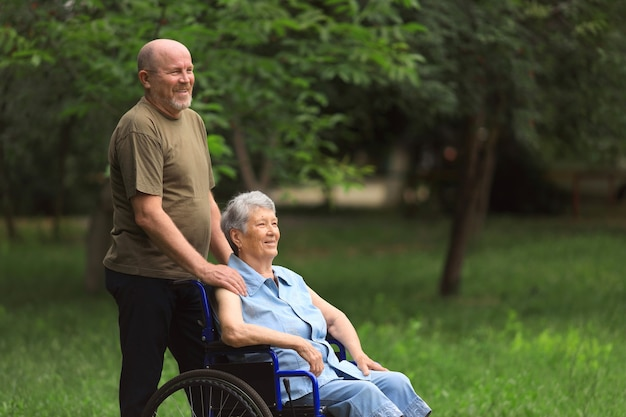 Happy elderly man walking with disabled elderly woman sitting in wheelchair outdoors