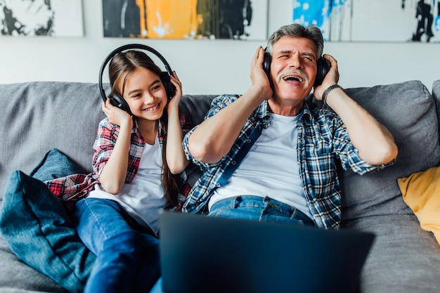 Happy elderly man with a little girl is using a headphones while lying at home.