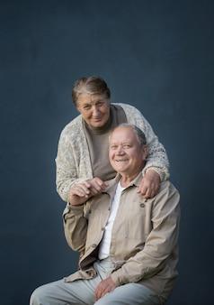 Happy elderly married couple on blue background