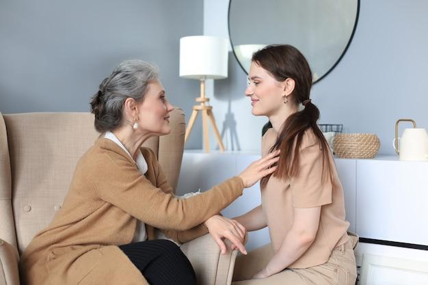 Счастливая пожилая средняя мать сидит на стуле, трогая прядь волос дочери, глядя друг на друга, доверенные отношения. семейное понятие.