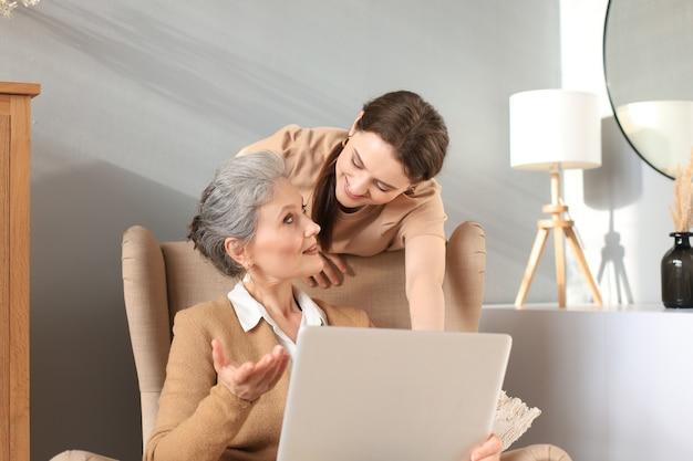 ラップトップを見て、娘と一緒に椅子に座っている幸せな高齢の中間の母親。ビデオ、写真をママに見せている若い女性、信頼できる関係。家族の概念。