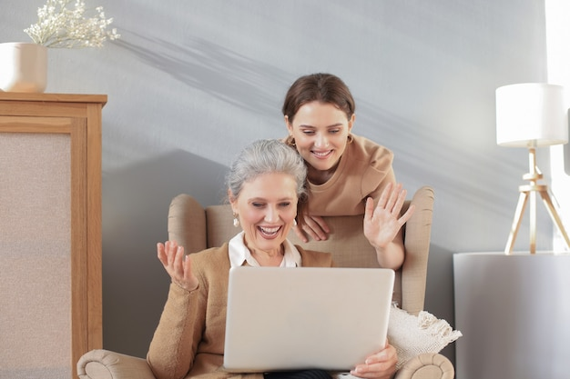 ラップトップを見て、娘と一緒に椅子に座って幸せな高齢の中間の母。ビデオ、写真をママに見せている若い女性、信頼できる関係。家族の概念。