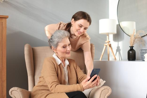 スマートフォンを見ながら、娘と一緒に椅子に座って幸せな高齢の中間の母。ビデオ、写真をママに見せている若い女性、信頼できる関係。家族の概念。