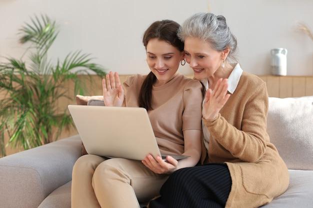ラップトップを見ながら、娘と一緒にソファに座っている幸せな年配の中間の母親。ビデオ、写真をママに見せている若い女性、信頼できる関係。家族の概念。