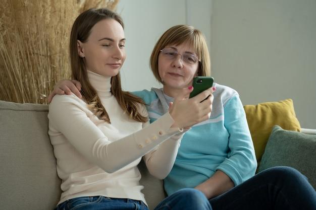 행복한 노인 엄마는 스마트 폰 딸을보고 딸과 함께 소파에 앉아 노인 어머니에게 휴대 전화를 사용하도록 가르칩니다.
