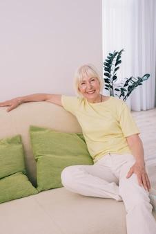 Счастливая пожилая старая веселая кавказская стильная женщина с седыми волосами сидит на диване у себя дома
