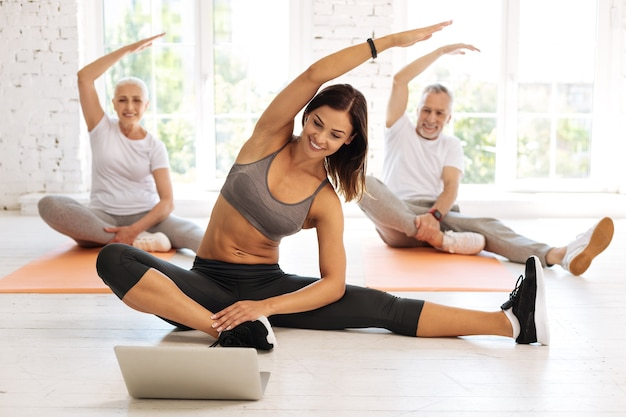 Happy elderly people sitting on mats behind their instructor and lifting arms while keeping smile on faces