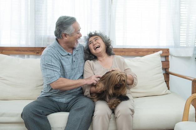 幸せな高齢者シニアアジアカップルは、介護保育園でペット療法と一緒にソファーに座って、引退した男と自宅のリビングルームのソファに座っている女性持株犬。