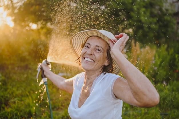 여름 정원에서 호스로 식물에 물을 주는 것을 즐기는 행복한 노년 여성