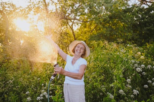 Happy elderly senior woman having fun watering plants with hose in summer garden drops of water in