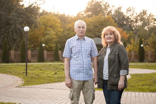 Happy elderly seniors couple in summer park, valentines day