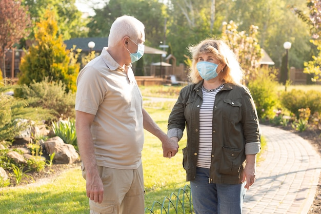 Happy elderly seniors couple wearing medical mask to protect from coronavirus in summer park