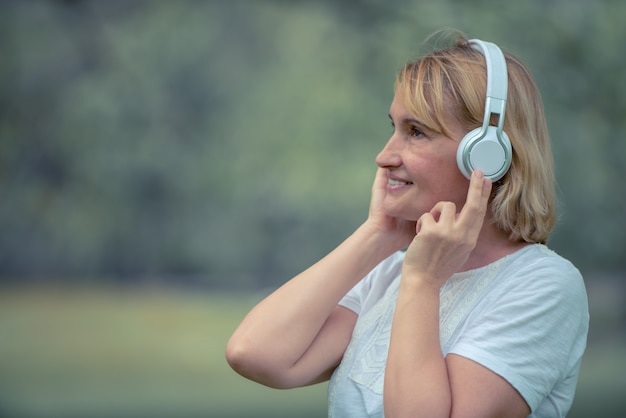 Happy elderly woman listening music on headphone in the park