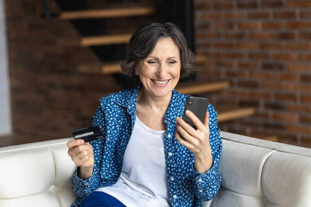自宅のソファに座って電話を使用してクレジットカードで支払う幸せな年配の女性。ショッピングオンラインコンセプト