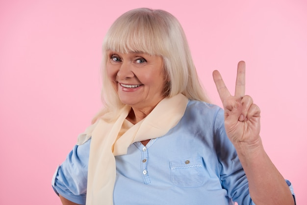 Happy elderly woman shows victory sign.