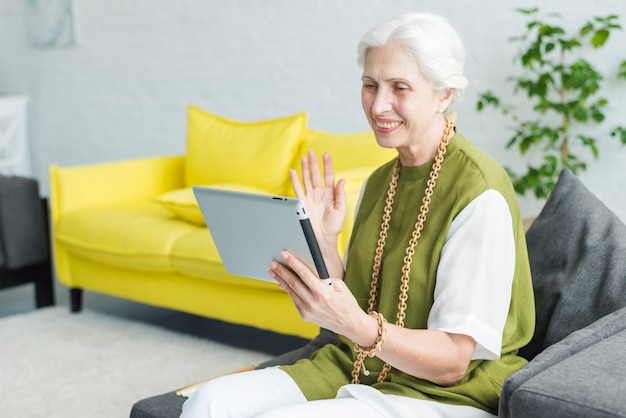 Happy elderly woman sitting on sofa looking at digital tablet waving her hand
