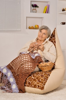 Happy elderly woman sitting with knitting  on armchair