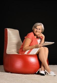Счастливая пожилая женщина, сидящая с газетой на красном кресле