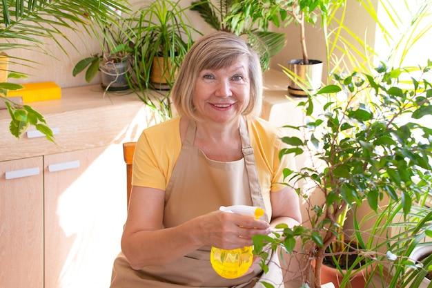 스프레이 병으로 식물을 살포하는 행복한 노인 여성 수석 여성과 식물을 돌보는
