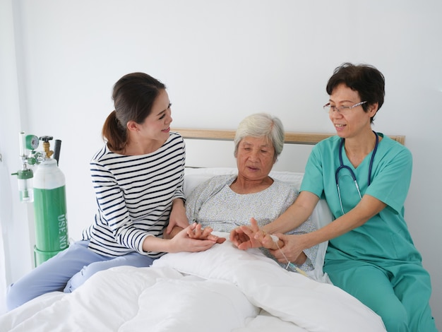 Happy elderly woman talking with senior nurse and her daughter in hospital room.