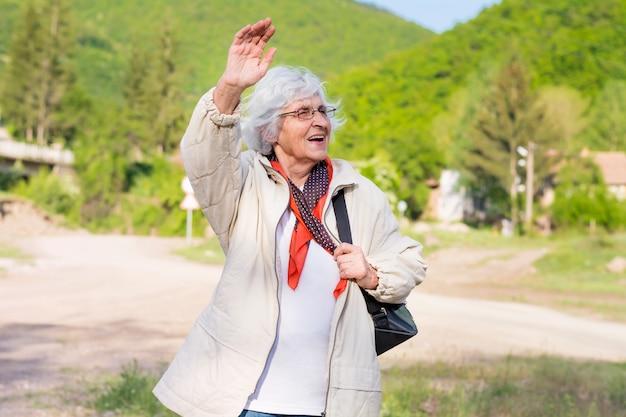 Felice anziana donna che cammina in campagna