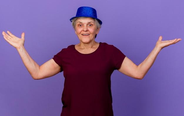 パーティーハットを身に着けている幸せな年配の女性は、コピースペースと紫色の壁に分離された手を開いて保持します。