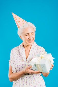 Happy elderly woman with birthday gift on blue backdrop