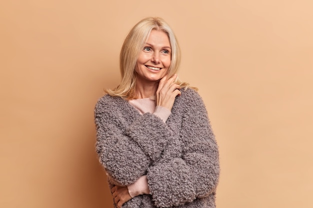 ブロンドの髪を持つ幸せな年配の女性は、ベージュの壁に対してファッショナブルな冬のコートのポーズを着てどこかに焦点を当てた夢のように見えます
