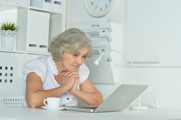 사무실에서 노트북 작업을 하는 행복한 할머니