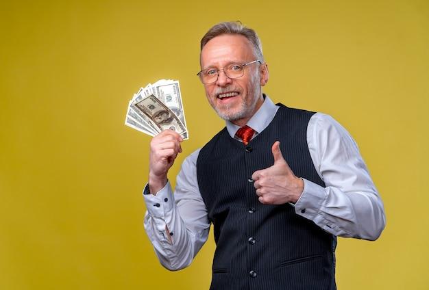 黄色の背景に分離されたドル紙幣のファンと幸せな高齢者のビジネスマン。