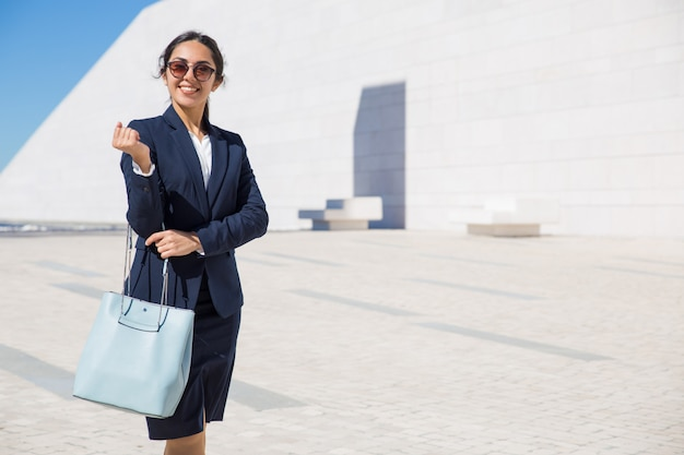 Happy elegant business lady heading to her office