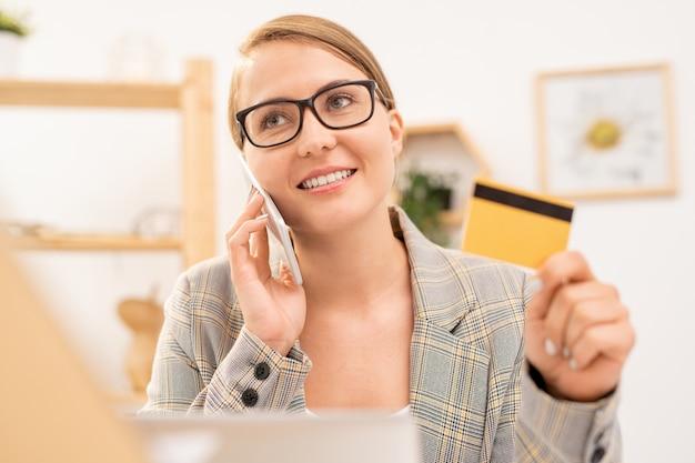 オンラインショップで商品を選択した後電話で注文眼鏡の幸せなエレガントな実業家