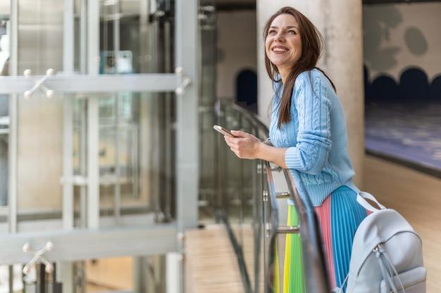 免税ショッピングモールでリラックスしてスマートフォンを使用して立っている荷物を持つ幸せなエレガントな旅行の女性