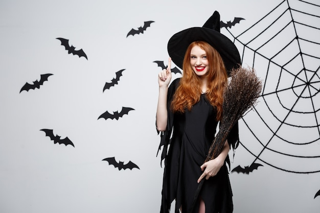 Happy elegant witch with broomstick halloween doing pointing finger on side.