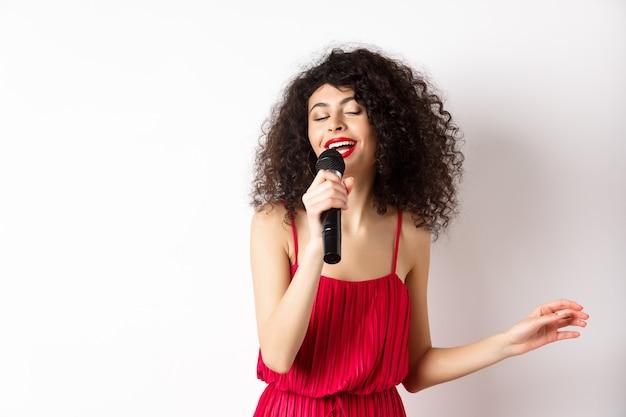 マイクで演奏し、カラオケを歌い、笑顔で、白い背景の上に立って赤いドレスを着た幸せなエレガントな女性。