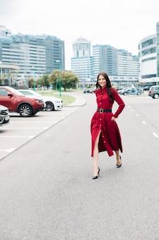 Happy elegant woman in red on road