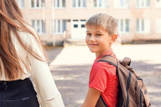 学校に行く幸せな小学生の男子生徒