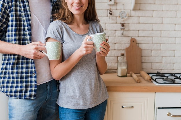 Happy embracing couple drinking brew and standing in kitchen