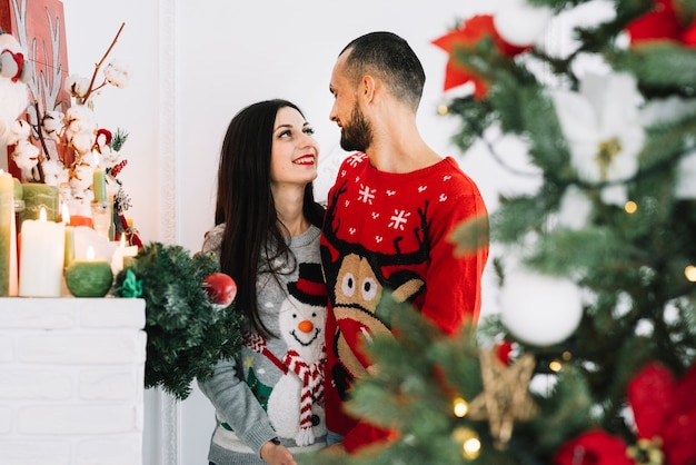 Happy embracing couple near candles and fir tree